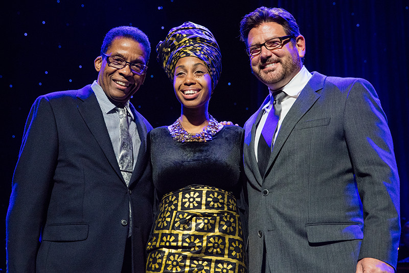 Institute Chairman Herbie Hancock (l) and Concord Music Group President John Burk (r) congratulate 2015 Monk Vocals Competition Winner Jazzmeia Horn following the Competition Finals at the Dolby Theatre in Hollywood, CA.